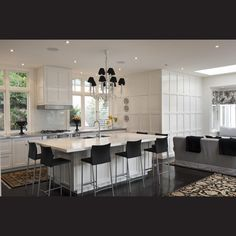 The monochromatic interior colour scheme, referenced throughout the renovation, is seen in the kitchen in the black bar stools and a custom painted, black-and-white chandelier.