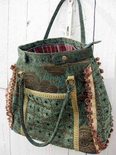 Large bag made of heavy tapestry fabric in green, gold, and burgundy. Lined in a striped coordinating fabric that is easy to keep clean. Lots