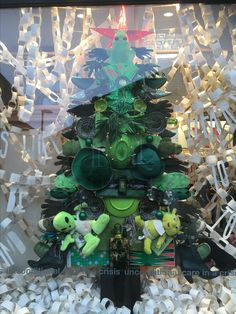 "2016 #HayonWye #RedCross charity shop Christmas window/visual merchandising. Display entirely made from shop donations - Christmas tree made from green objects/toys/shoes, book/wallpaper #paperchains and #DrSeus quote cut from pages: ""Christmas will always be as long as we stand heart to heart and hand to hand"", from #Thegrinchwhostolechristmas. Window made by Emily Daw #charityshop #christmaswindow #visualmerchandising"