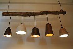Met een grote tak en een paar leuke lampjes creëer je een mooie lamp voor boven de tafel.