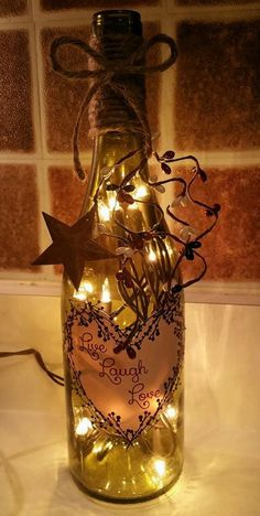 Live Laugh Love Primitive Heart wine bottle light decorated with pips and berries and a metal star. Shape of bottle may be slightly different depending on stock but will be the same color.