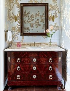 Gracie wallpaper lines a powder room at this art-collecting Houston couple's home. The vanity was made from a Directoire commode. #bathroom #interiordesign