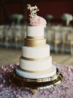 Gold and white wedding cake topped with a pink peony flower. Photography: Laura Gordon - www.lauragordonphotography.com