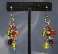 These unique up-cycled earrings were created from the beads of a bracelet found in a local thrift store. A mix of colored glass, plastic and wooden beads of varying sizes and shapes are clustered together on a brass tone chain. They measure approximately 2 and 1/2 from the hole and are finished with new brass tone fish hooks and rubber stoppers. You can find a slight variation on this piece here: https://www.etsy.com/listing/459853536/up-cycled-jewel-toned-bead-cluster  My jewelry is mostly…