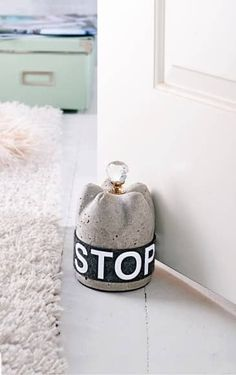 Concrete doorstop. Moulded and set with a crystal doorknob then fitted with a band saying 'door stop'.