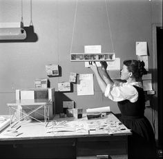 Ray Eames working with an architectural model.