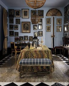 Spanish Conquest: An 18th-century rug covers a table in the entrance hall; the bench is in the Régence style, the desk is by Marc du Plantier, and 18th-century engravings fill the walls.
