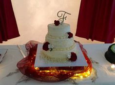 Ivory 3 tiered round wedding cake; with red/ivory roses -