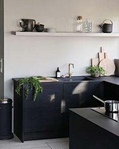 meuble bleu canard, mur blanc avec étagère blanche, mur noir avec des fourneaux, évier en couleur or, carrelage blanc