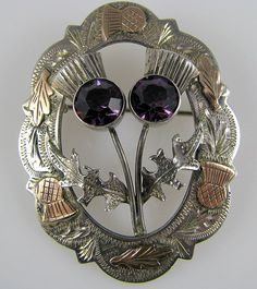 This sterling silver brooch features double thistles of faceted amethyst colored pastes