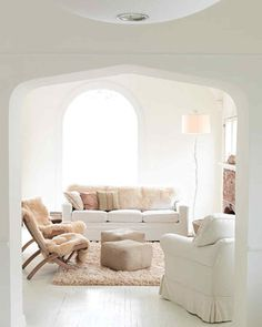 Neutral living room design with a white, beige, and tan color scheme featuring lots of texture from the cream shag area rug to the sheepskin throws on the side chairs and sofa - Neutral Home Ideas & Decor
