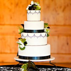 Black Scallops and Green Blooms  Black scalloped edging and clusters of green-and-black blooms mimicked the wedding style on the four-tiered, white, fondant-covered cake.