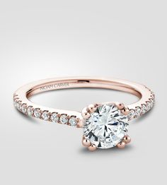 Stunning classic in rose gold.   Engagement ring by Noam Carver, featuring a round centrepiece and 22 diamonds on the band.