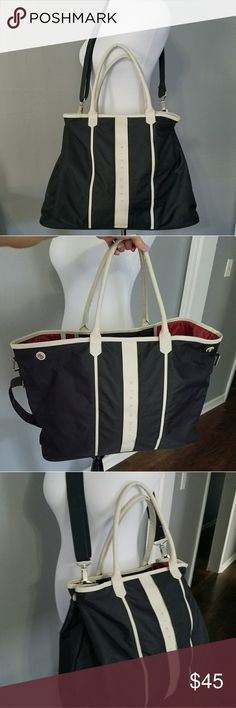 Nike Golf Black Tote Bag Large tote bag with cross body strap. Black and ivory color. Interior pockets. Outside can be expanded or taken in at the snaps. Only sign of use and only flaw is shown in last picture. Nike Bags Totes