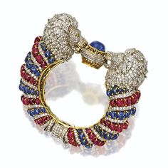 Sapphire, ruby and diamond 'lion's-head' bangle-bracelet. The hinged bangle designed as two confronting lions' heads centering a cabochon sapphire, the faces and manes pavé-set with round diamonds, their eyes set with 4 small round diamonds of yellow hue, the bodies froming the bracelet sides decorated with stripes of cabochon rubies and cabochon sapphires alternating with bands of round diamonds, the total diamond weight 22.75 carats, mounted in gold and silver.
