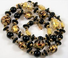 Vintage Murano Italy art glass lampwork beaded necklace Clear glass with 24k embedded gold foil centers and black swirls Hand knotted with black silk Screw barrel clasp 24 inches long Unsigned I have matching earrings, please contact me, it should be available in my earrings section