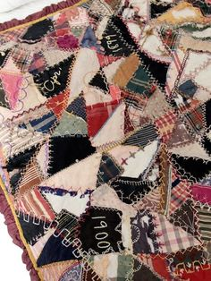 """A rare double sided patchwork crazy quilt circa 1898. Hand-stitched at the turn of the century, the quilt features """"crazy"""" quilt patchwork on one side, and a log cabin quilt pattern on the other. The """"crazy"""" quilted side features hand-embroidered months and years. The quilt has a ruffled burgundy trim. double-sided quilt hand-stitched hand embroidered dates crazy patchwork and log cabin patchwork ruffle hem CONDITION In good condition with wear consistent with age and us..."""