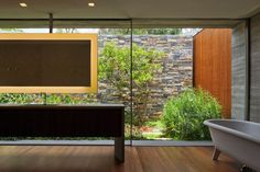 V4 house / Studio mk27 . Marcio Kogan + Renata Furlanetto . indoors outdoors . glass wall opening to walled patio running legnth of room