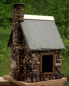 Rock log cabin style birdhouse with slate roof