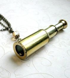"This fun brass telescope necklace comes on a sturdy, long 28'' brass chain. This beauty is a miniature working telescope, which retracts and opens, made from solid brass. The telescope comes on a sturdy brass chain. It is a great statement piece, perfect for sailors and explorers alike. Telescope measures: 3 1/4"" long when expanded."