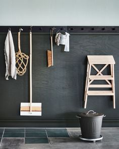 Cleaning tools like a mop and heavy brish hango on a wall above a bucket.