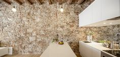 Architect Sergi Pons placed a white minimalist cube at the center of this renovated apartment in the Les Corts neighborhood in Barcelona, Spain, which creates a stunning effect against the original stone wall and wooden beams on the ceiling. Spanish Apartment, Zeitgenössisches Apartment, Apartment Renovation, Mini Loft, Kitchen Stone Wall, Barcelona Apartment, Journal Du Design, Timber Beams, Interior Architecture