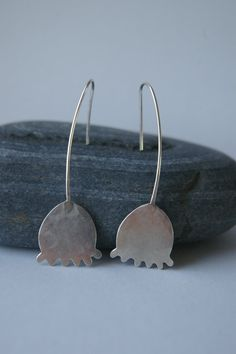 These simple and elegant earrings are handmade in solid sterling silver.    I cut out the shapes by hand, solder on the earwire stem, then hammer to