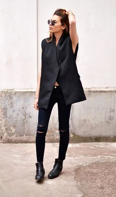 Maja Wyh in a black tuxedo vest, black jeans, and black ankle booties