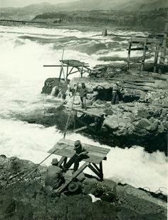 Four North American Indians are fishing from platforms at Celilo Falls on the Columbia River. A net lies on one of the platforms. A bridge is in the background. - Washington State Historical Society