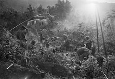 Marines emerge from their foxholes south of the DMZ after a third night of fighting against North Vietnamese troops in September 1966. The helicopter on the left was shot down when it came in to resupply the unit  Photograph: Henri Huet/AP