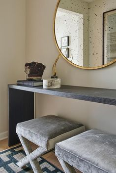 Chic foyer features a pair of gray velvet x stools, atop a gray and blue rug, tucked under a black waterfall console table and a round brass mirror. Formal Living Rooms, Home Living Room, Apartment Living, Entrance Rug, Entry Foyer, Foyer Decorating, Trends, Interior Design Studio, Contemporary Furniture