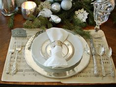 Antique sheet music makes a chic, unconventional base for this white-and-silver place setting. Top the music with a silver charger, an ironstone dinner plate and a silver bread plate. Then, roll up a monogrammed linen napkin in a simple silver ring. Photo by Marian Parsons; Create a Classic Silver and White Tablescape>>