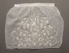 Apron, 18th century. Fine white cotton or linen with whitework embroidery and drawn work in design of flowers and leaves.