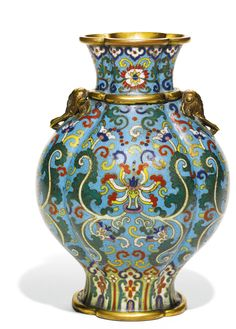 A CLOISONNÉ ENAMEL 'LOTUS' VASE QING DYNASTY, 19TH CENTURY of quatrelobed form, rising from a spreading foot to a waisted neck flanked by a pair of gilt-bronze elephant handles, the exterior brightly decorated with stylised lotus sprays above lappet and ruyi bands, all below stylised floral sprays below ruyi heads, the rim, shoulder and foot encircled by raised gilt-bronze fillets, Japanese wood box