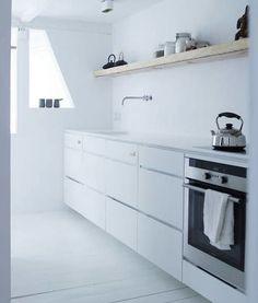 White kitchen with wooden shelf