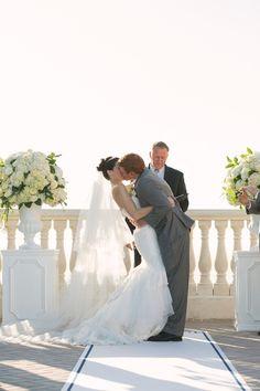 Bride and Groom Wedding Ceremony Kiss | Classic, Elegant White Wedding Ceremony Decor Flowers on Pedestal | Clearwater Beach Hotel Wedding Venue | Hyatt Regency Clearwater Sky Terrace Outdoor Ceremony