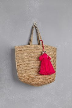 A large straw tote bag by Shiraleah™ featuring metallic accents throughout and an oversized tassel with a high-polish etched beaded detail.