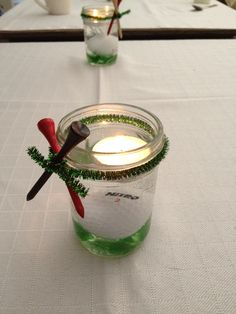 My sister's center pieces for Father's Day! Mason jar, green glass pieces and golf ball in water with floating candle, and green fuzzy sticks holding golf tees on! Cute!