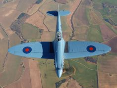 The RAF's BBMF PR XIX Spitfire in flight over the English countryside.