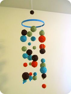 DIY yarn mobile. @Rachel Drabick  made two like this with less balls and embroidery hoop for church nursery