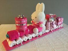 Foto: Luiertrein voor een meisje | Benodigdheden: 15 luiers, maat 2, voor het onderstel, 1 roze handdoek, 1 speen, 1 roze Nijntje, 1 kerstbal 'my first christmas' voor de voorkant, 1 roze mandje voor de cadeautjes, 1 kubus voor het achterstel, 10 meter gekleurd lint, 1 houten (kindermeetlat) voor de onderkant | Succes en veel plezier met geven!.