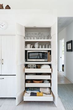 Save counter space by stowing microwave, toaster and other small appliances in a cabinet with pull out shelves and hidden outlets.  Shiela Narusawa's Cape Cod Kitchen Photographed by Matthew Williams for Remodelista (scheduled via http://www.tailwindapp.com?utm_source=pinterest&utm_medium=twpin&utm_content=post145224139&utm_campaign=scheduler_attribution)