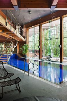 This elegant contemporary home was completed by the architect Olga Freiman. The house has been designed with a blend of steel, glass and wood, the indoor swimming pool room looks magnificent, with large floor to ceiling windows and a unique staircase hovering above the pool.  Located near to Moscow, Russia.