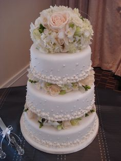 Beautiful 3 tier off white wedding cake decorated with fresh flowers in between each tier and as topper.  This wedding had the beautiful backdrop of Taboo Resort  www.cakesbydesign.ca