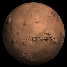 Компьютерная модель Марса. Слева — гора Олимп. Это потухший вулкан и самая высокая гора в Солнечной системе высотой 26.2 км. Атмосферное давление на вершине Олимпа составляет лишь 2 % от давления, характерного для среднего уровня марсианской поверхности. Для сравнения, высота Эвереста составляет 8.8 км, а давление на вершине Эвереста составляет 25 % от показателя на уровне моря