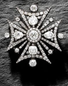 A diamond-set Maltese cross brooch/pendant, circa 1820 The arms of the cross alternating with floral tines, set throughout with cushion-shaped diamonds with pear-shaped diamond highlights, with a cushion-shaped diamond cluster to the centre, mounted in silver and gold, diamonds approx. 12.90cts total, length 5.1cm