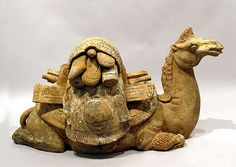 Reclining Camel with saddle bundle   China; Tang Dynasty  618-907 CE  Painted earthenware