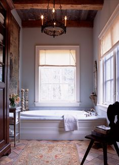A Persian carpet is an unusually luxurious choice for a bathroom, but stands up well to wear and tear. An antique wrought-iron chandelier from Europe illuminates the tub area. To the left, a display c