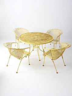 A Vintage Patio Table And Four Chairs The Yellow Metal Mesh Set Features Vine Patterns On Backs Of Round Center
