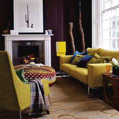 love the moody wall colour with the chartreuse sofa and ottoman  via Keltainen talo rannalla